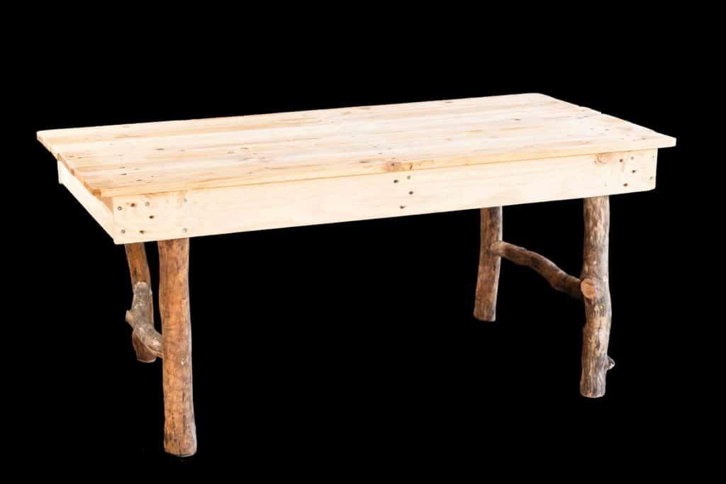 Table en bois recyclé sur fond noir.