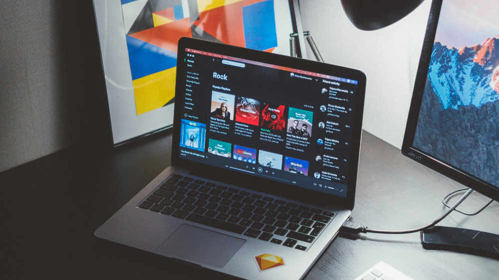 Ordinateur sur bureau avec Spotify pour un design graphique ou Médiamaticien